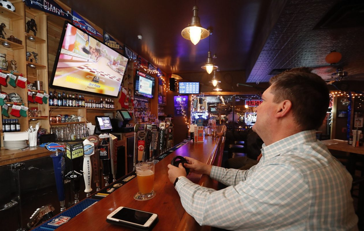 Nathan Mertz enjoys a beer and a game of Mario Kart 8 at Rookies in East Aurora. Every Wednesday is game night. (Mark Mulville/Buffalo News)