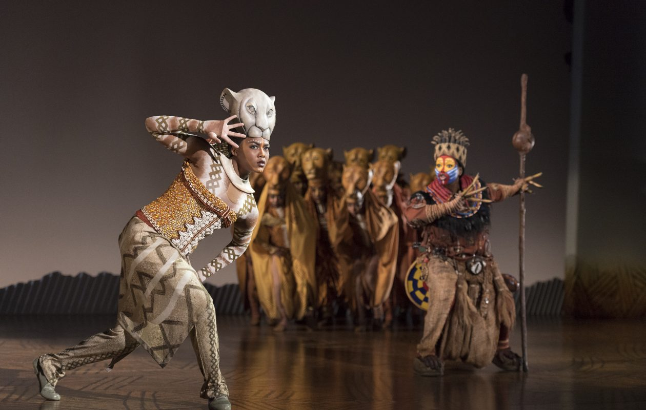Nia Holloway, left, plays Nala and Buyi Zama  plays Rafiki (with staff) in the touring production of The Lion King at Sheas Performing Arts Center.