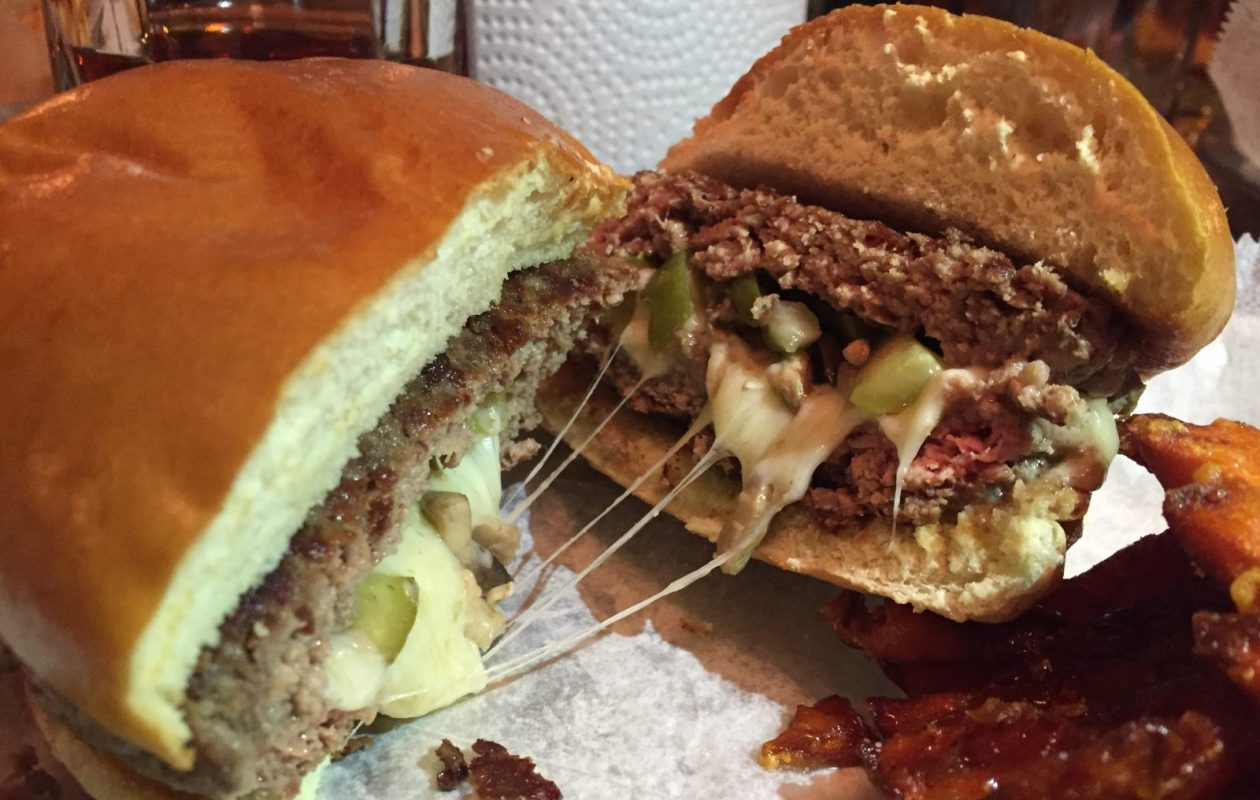 The molten cheese core of a Swiss cheese, mushroom, and pickle 'Stooge' at Stooges Stuffed Burger Bar in Lockport (Phil Wagner/Special to The News)