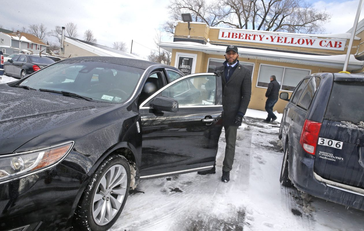 Liberty Yellow Cab executive class taxi driver Tyrell Adams with one of the firm's new Lincolns on Kenmore Avenue in Kenmore.  (Robert Kirkham/Buffalo News)