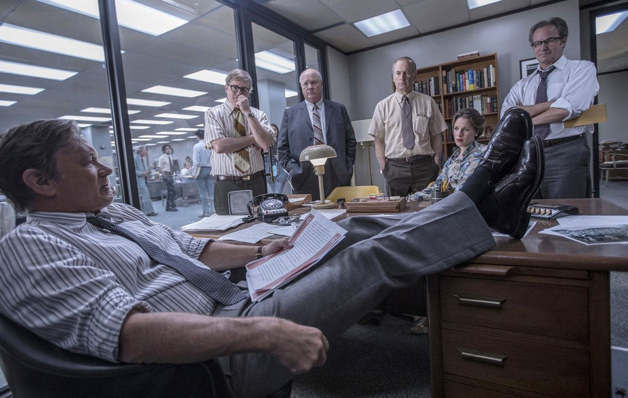 """Washington Post editor Ben Bradlee (Tom Hanks), in foreground, confers with members of the newspaper's staff, played by, from left, David Cross, John Rue, Bob Odenkirk, Jessie Mueller and Philip Casnoff, in """"The Post."""" (Niko Tavernise/Twentieth Century Fox)"""