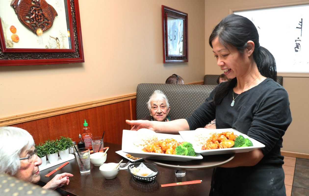 Wok & Roll is in Williamsville Place Plaza at 5467 Sheridan Drive in Williamsville. Cindy Xue serves customers Getelle Rein, left,  and Sylvia Wishnoff their lunch. (Sharon Cantillon/Buffalo News)