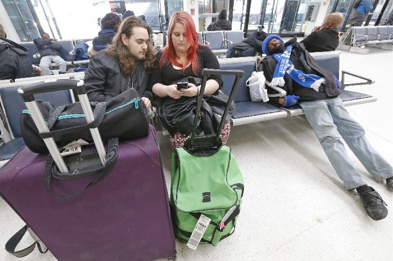 Lucas Plumridge and Courtney Craig wait in Buffalo for their final bus back to Syracuse. The couple started out in Cleveland Saturday and the whole trip will be close to a 24 hour ordeal.  They were among many Greyhound passengers whose holiday trips took a bad turn due to weather and driver shortages. (Robert Kirkham/Buffalo News)