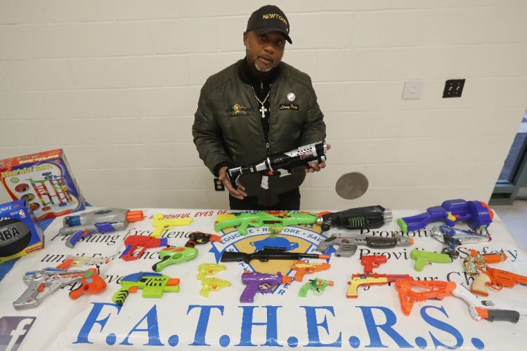 Leonard Lane, president of FATHERS, displays  some of the toy guns the group collected at the Delavan-Grider Community Center. They exchanged the toy guns for non-violent holiday gifts. (Mark Mulville/Buffalo News)