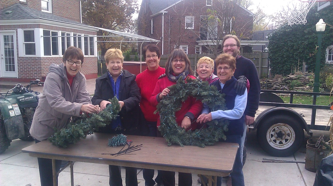 Members of the Kenmore Village Improvement Society prepare wreaths to hang along Delaware Avenue. (Mike Ham/Kenwood Photography)