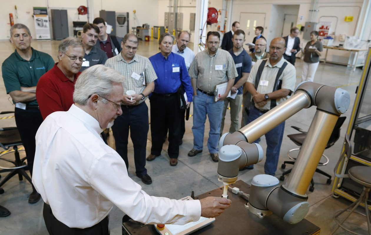 Ron Brown, technology leader, flexible manufacturing for EWI, shows off a new 'cobot' a robot that can safely interact with human workers, during a tour of Buffalo Manufacturing Works.  (Derek Gee/Buffalo News)