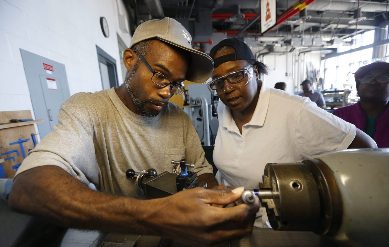 Eric Artis, left, and classmate Ruby Laster, both of Buffalo work on a metal lathe machine at one of SUNY Buffalo States new tech classes in metal working and machining.  (Robert Kirkham/Buffalo News)