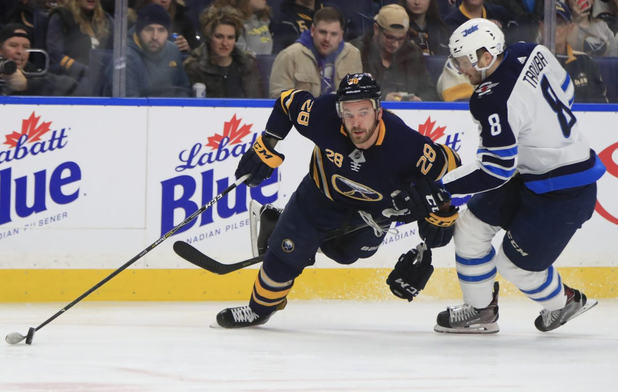 Sabres winger Zemgus Girgensons is hooked by Winnipeg defenseman Jacob Trouba during first-period action (Harry Scull Jr./Buffalo News).
