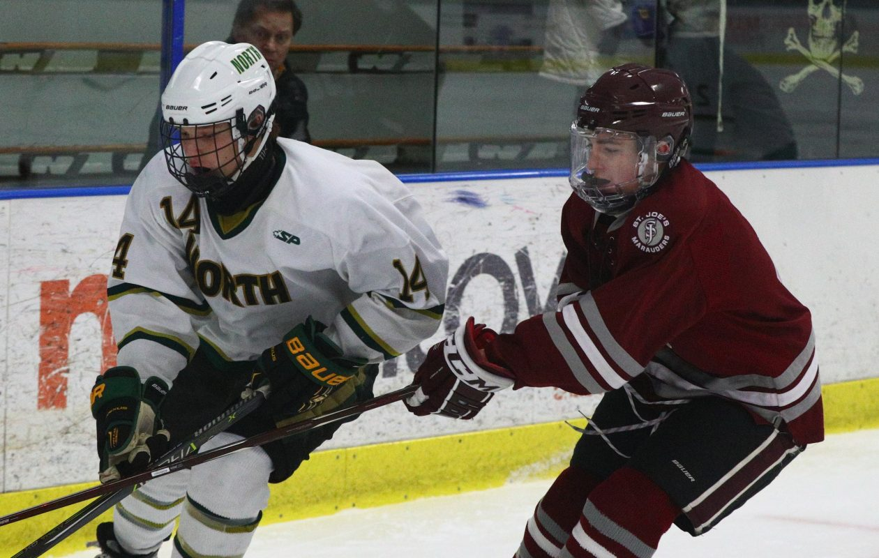 St. Joe's Patrick Gilbert battles Williamsville North's Kevin Martin during a 3-1 Spartans win at Northtown Center Friday. (James P. McCoy/Buffalo News)