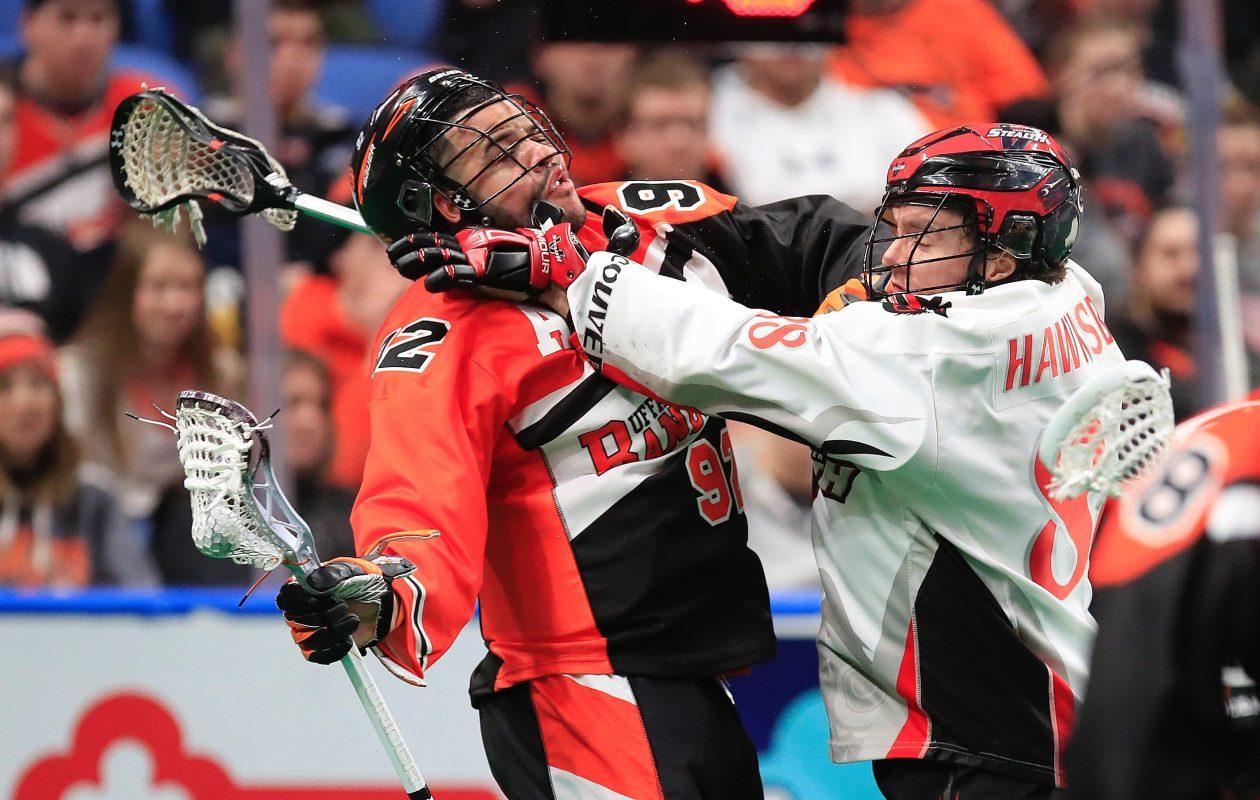 Buffalo Bandits forward Dhane Smith takes a high hit from Vancouver's Ian Hawksbee. (Harry Scull, Jr./Buffalo News)