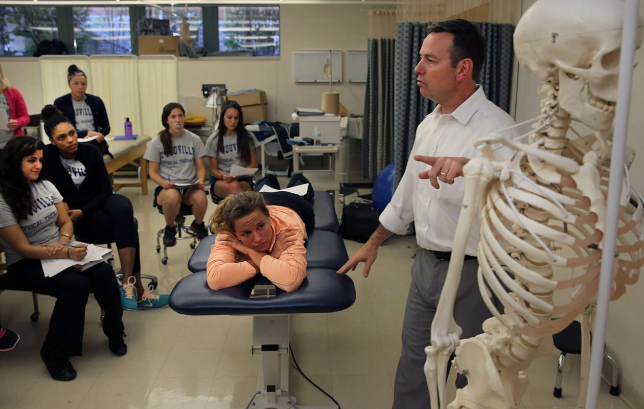 Professor Ron White refers to a model skeleton during a functional anatomy class for physical therapy students at D'Youville College. (Buffalo News file photo)