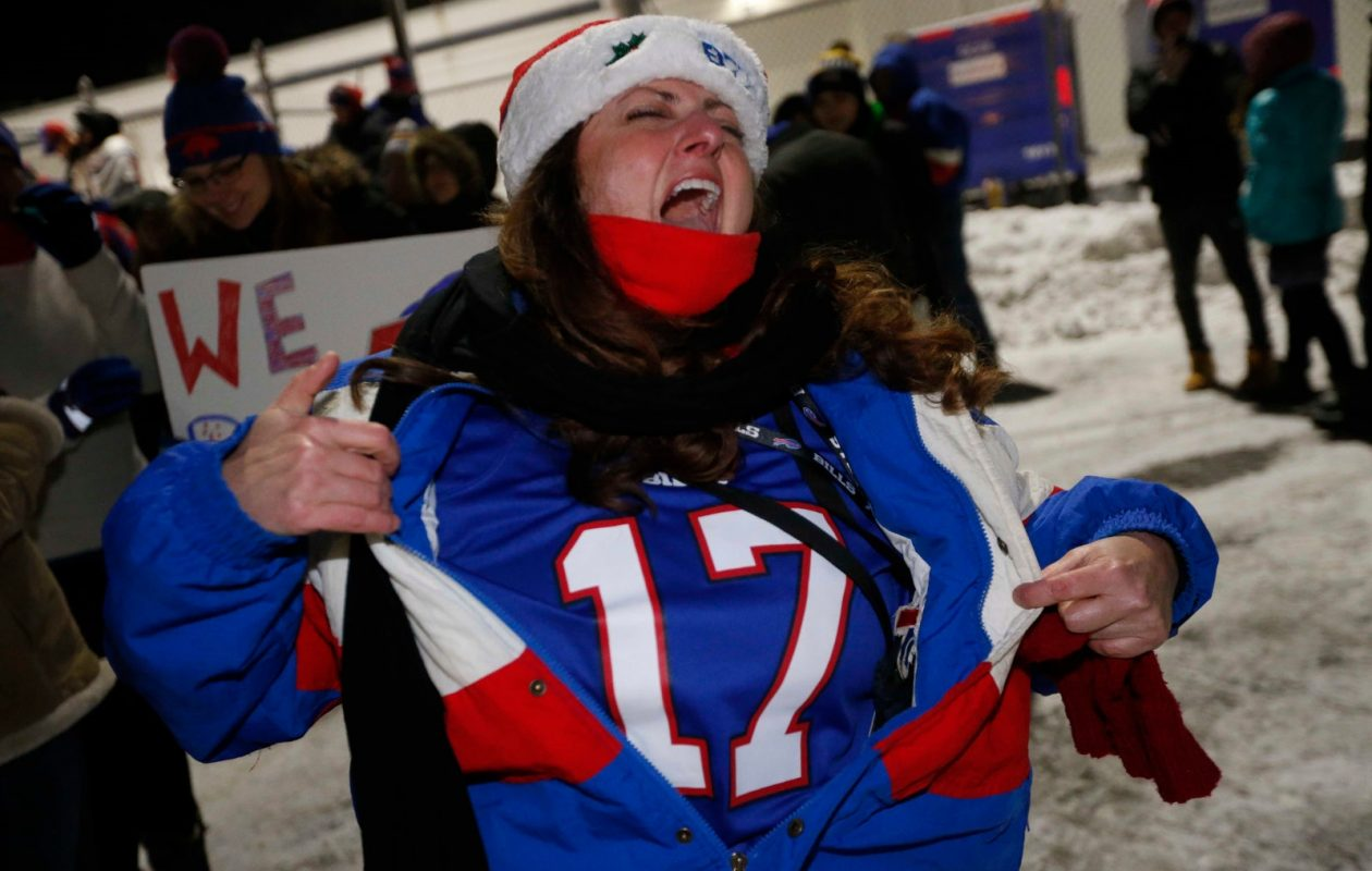 A jubilant Mary Ellen Bossert of Hamburg opens up her jacket as she shouts 'Seventeen years!' while welcoming the Bills home at the airport Dec. 31. (Derek Gee/Buffalo News)