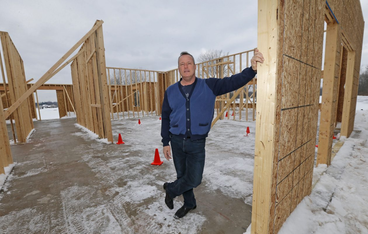 Timothy Davis stands in the framework of a clubhouse he's building at his Buffalo Tournament Club golf course in Lancaster. (Robert Kirkham/Buffalo News)