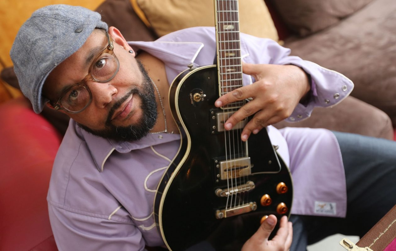 Eric Crittenden holds a guitar belonging to his late father, DJ Jones, who played with James Brown regularly during his prolific music career. (Derek Gee/Buffalo News)