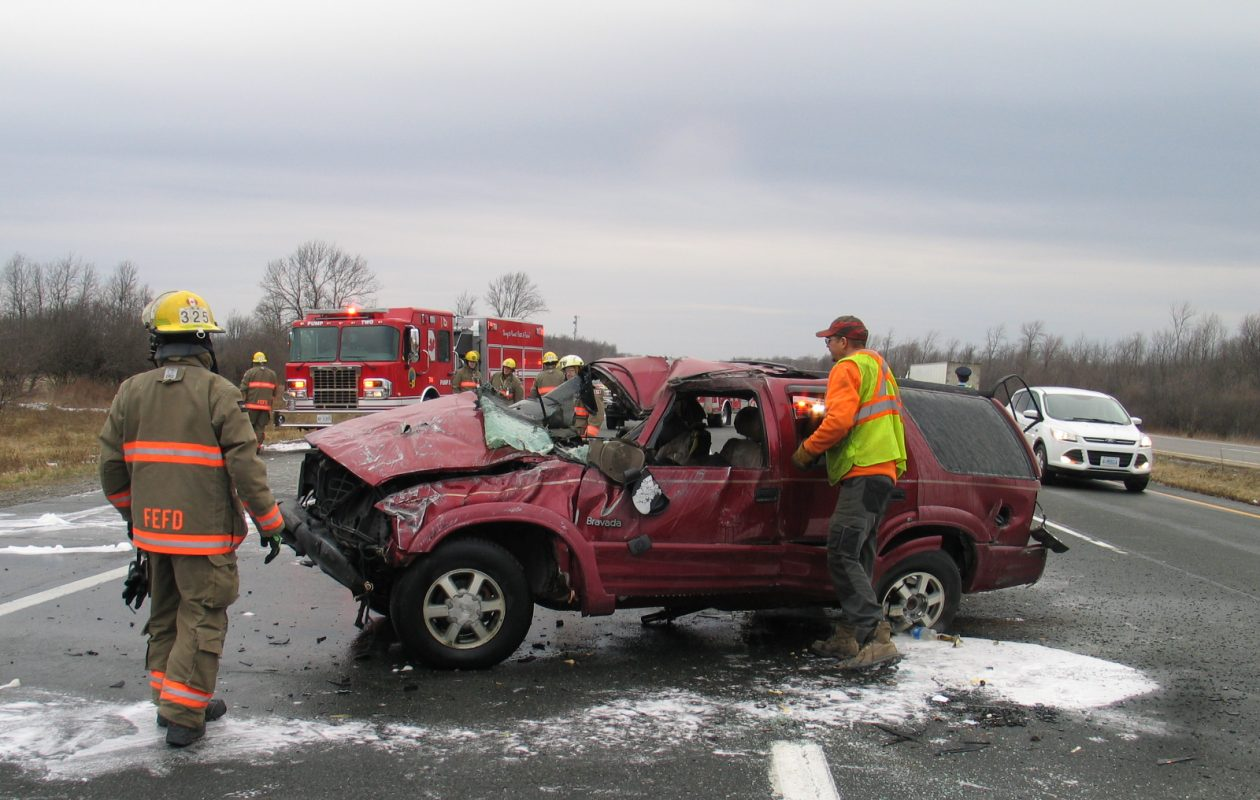 Fort Erie firefighters examine a burned-out SUV that crashed on the Queen Elizabeth Way Jan. 27, 2018. (Harry Rosettani/Special to The News)