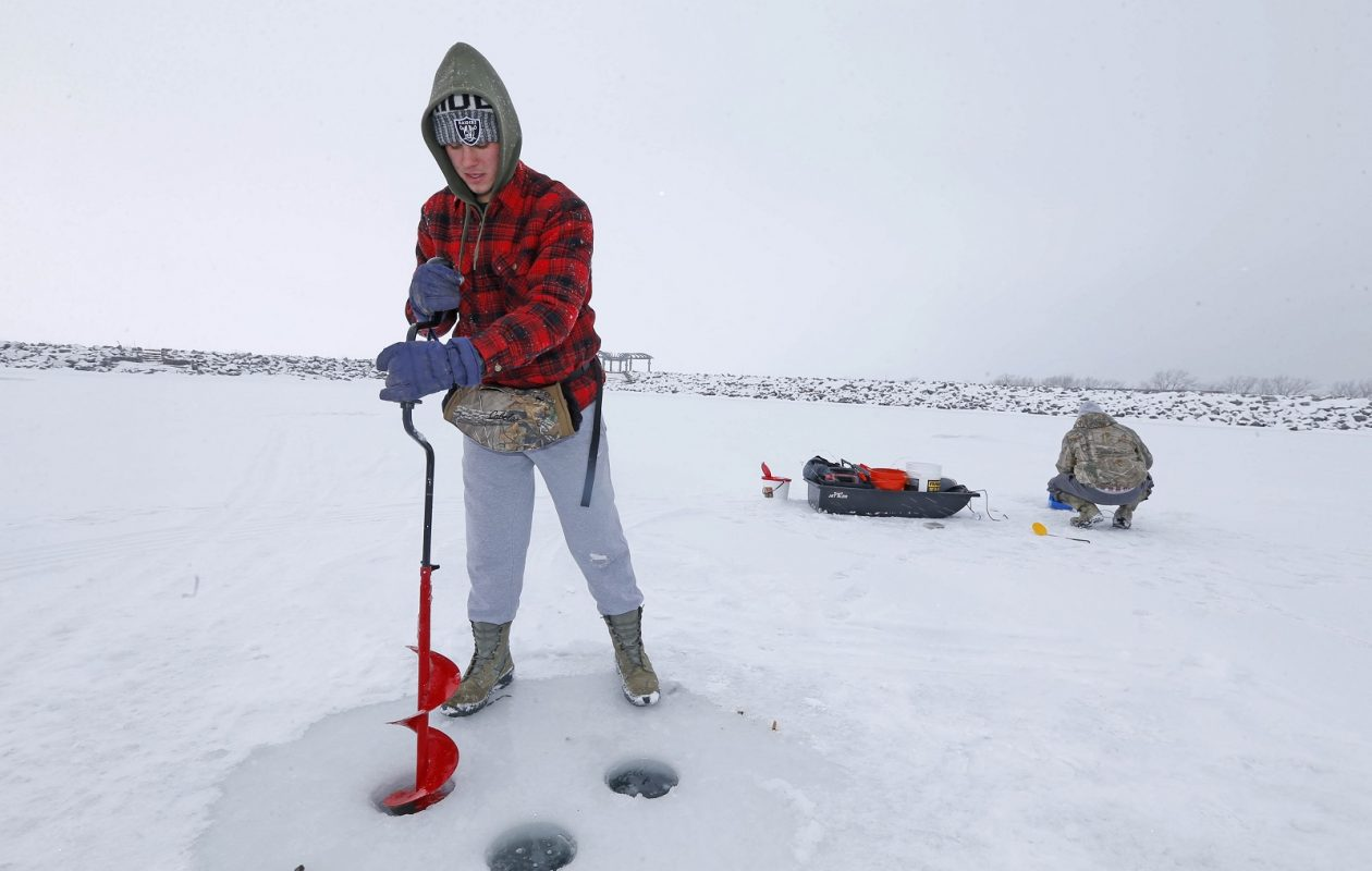 Its been cold enough for Nathaniel Fisk of Kenmore to set up for an afternoon of ice fishing on Lake Erie near the small boat harbor.  (Robert Kirkham/Buffalo News)