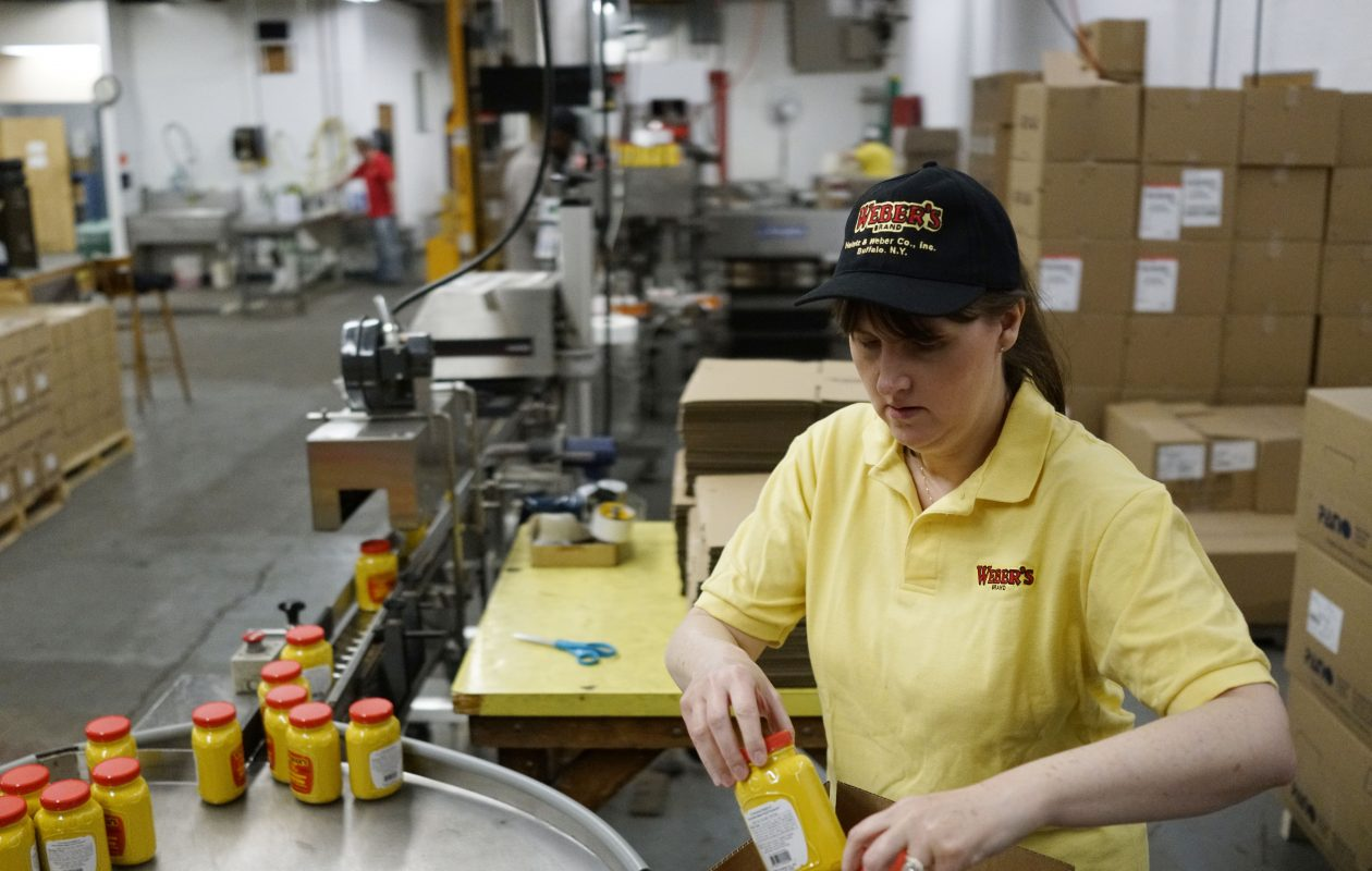 Suzanne Desmond, vice president of the Heintz & Weber Company, boxes freshly poured pints of Weber's Horseradish Mustard as they come off the bottling line at the company's South Buffalo facility. (Derek Gee/Buffalo News)