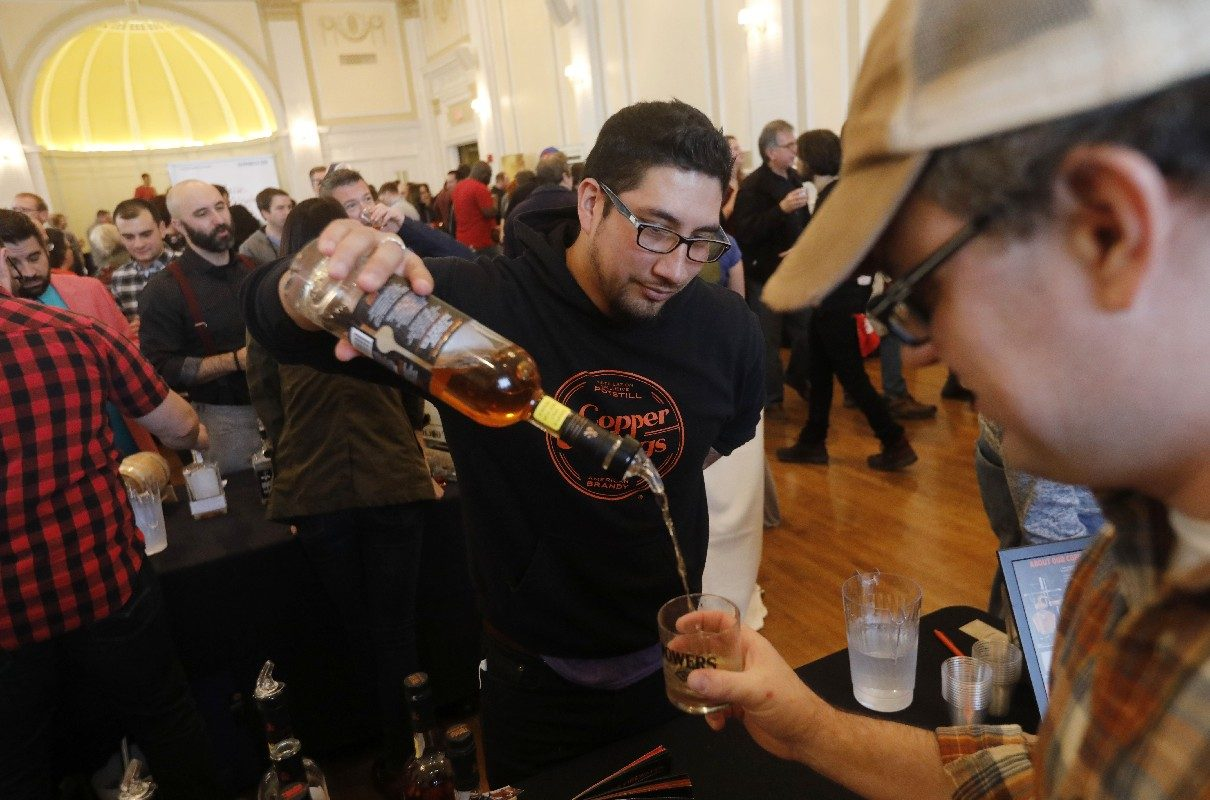 Eron Plevan of Copper & Kings in Louisville, Ky., pours an American brandy for Scott Miner of Cheektowaga during the first annual Whiskey Fest at Hotel @ The Lafayette. (Derek Gee/Buffalo News)