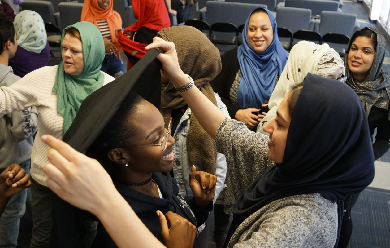 Junior Mariya Sami, 17, right, places a hijab over the head of senior Tionee Miller, 17, during an event to celebrate World Hijab Day at Leonardo da Vinci High School on Thursday.  Miller is one of dozens of students and faculty who volunteered to wear a hijab throughout the day for a cross-cultural experience. (Derek Gee/Buffalo News)