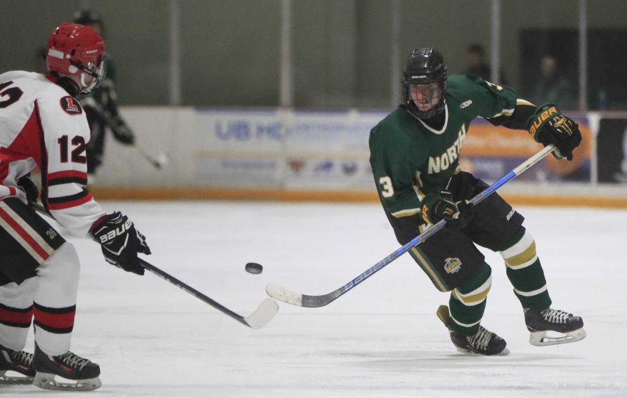 Brett Sardina flips a puck past Lancasters Jacob Bicknell during the third period of Williamsville North's 4-3 win Sunday at SUNY Buffalo State. Sardina scored twice to help the Spartans win the Division 1 title. (Harry Scull Jr./Buffalo News)