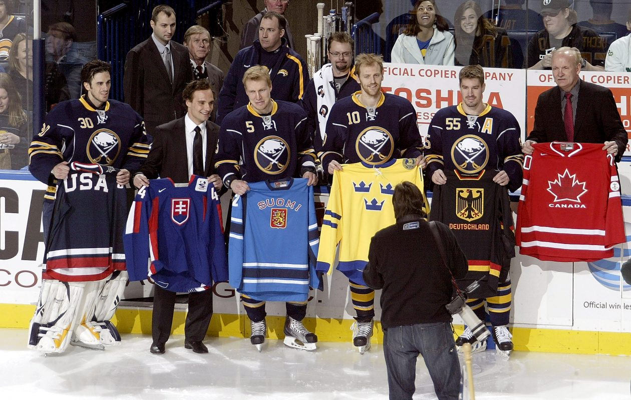 From left, Ryan Miller (30), Andrej Sekera, Toni Lydman (5), Henrik Tallinder (10), Jochen Hecht (55) and coach Lindy Ruff of the Buffalo Sabres display their respective Olympic jerseys of the countries they will represent during the XXI Olympic Winter Games in Vancouver, British Columbia, prior to playing the San Jose Sharks at HSBC Arena on Feb. 13, 2010, in Buffalo.  (Photo by Rick Stewart/Getty Images)