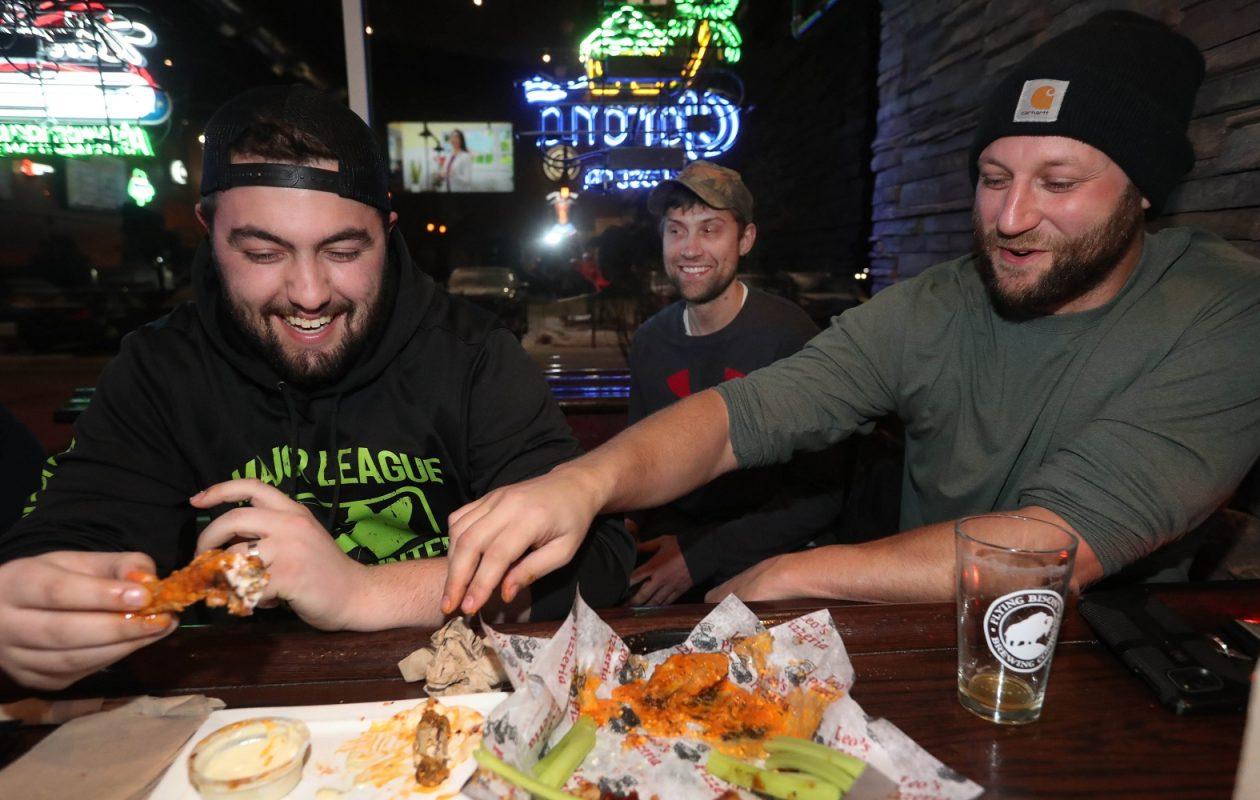 Jake Cislo, left, John Gajkowski and Brad Sutton enjoy some garlic parmesan wings at Leo's Pizzeria. (Sharon Cantillon/Buffalo News)
