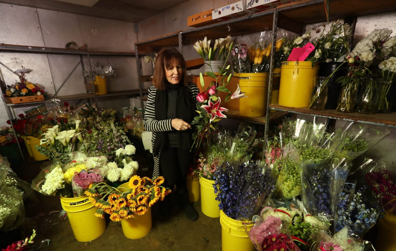 Maureens Buffalo Wholesale Flower Market owner Maureen Bartley gets  flowers from the cooler for an arrangement.  All flowers go into the cooler at night. (Sharon Cantillon/Buffalo News)
