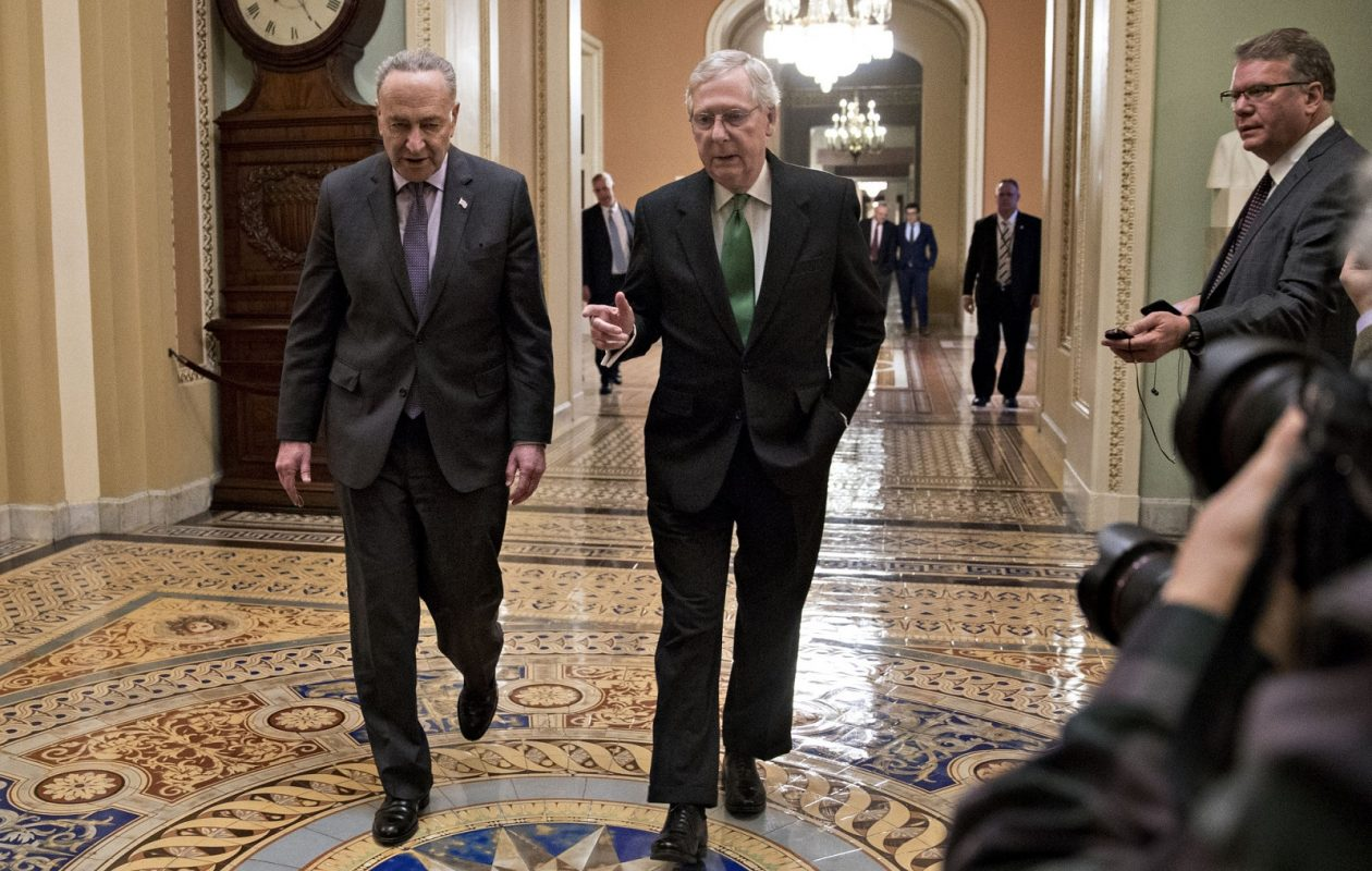 Senate Majority Leader Mitch McConnell, R-Ky. (right) talks to Senate Minority Leader Chuck Schumer, D-N.Y., Thursday while walking toward the Senate Chamber at the U.S. Capitol in Washington. The bipartisan budget deal the lawmakers crafted has exposed a rift in the Democratic Party over immigration.(Andrew Harrer/Bloomberg)