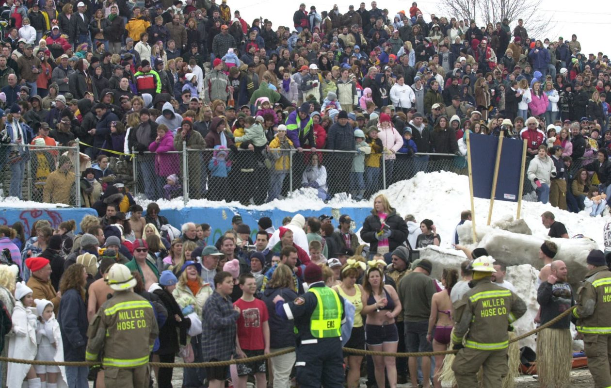 In this file photo, firefighters form a safety cordon and onlookers watch from above as Polar Bear Swim participants  dash into the open water at Krull Park Beach. This year's chilly dip will go on as scheduled despite severe water damage last spring.
