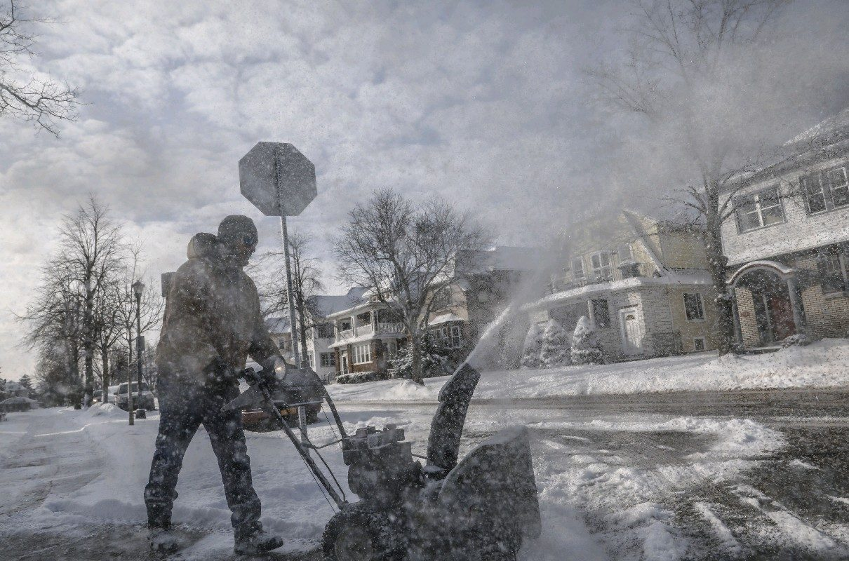 Bryan Banas uses a snowblower Tuesday to clear the sidewalk outside his home on Sterling Avenue in North Buffalo. (Derek Gee/Buffalo News)