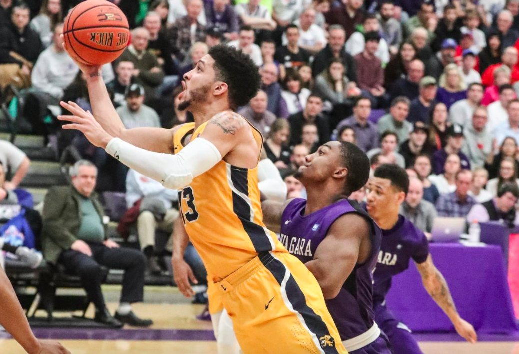Canisius Golden Griffins guard Isaiah Reese (13) scores two points over Niagara Purple Eagles guard Chris Barton (0) in the second half in the Gallagher Center at Niagara University in Lewiston NY on Wednesday, Feb. 21, 2018.  (James P. McCoy / Buffalo News