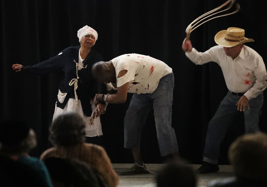 """Blood splatters as a slave auctioneer lashes a young black man while his mother wails over her family being torn apart in """"The Auction Block"""" performed by Mount Olive Baptist Church's Theater Ministry. The actors are, from left, Anita Guess, Charles Clancy and Robert Jenkins. (Sharon Cantillon/Buffalo News)"""