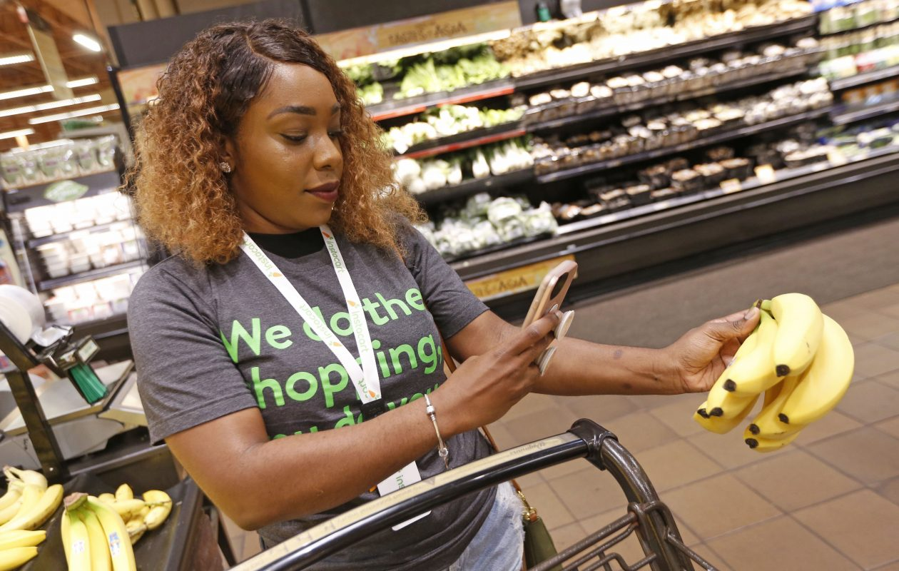Professional shopper Brianna Johnson of Buffalo uses her smart phone and the app to shop and scan for a customer's order at the Wegman's location on Alberta Dr. in Amherst.  (Robert Kirkham/Buffalo News)