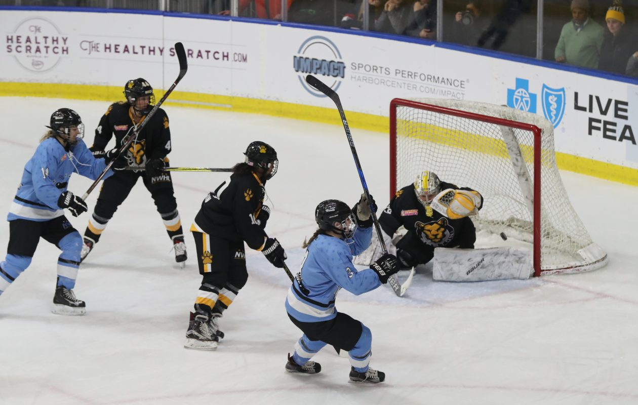 The Buffalo Beauts' Sarah Edney scores a goal on Boston Pride's Brittany Ott during the first  period. (James P. McCoy / Buffalo News)
