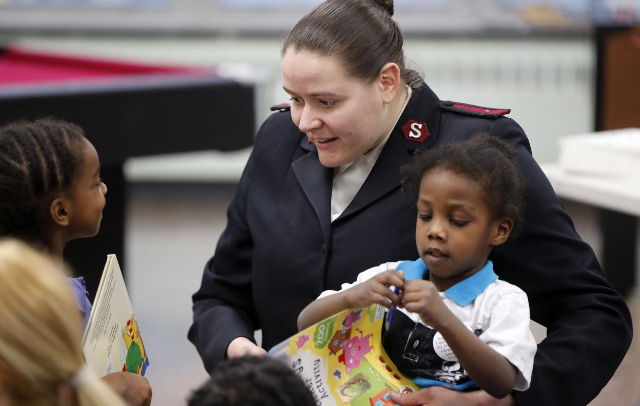 Lt. Allison Bethel reads to children during the Books for Kids 2018 Campaign Kickoff Tuesday at the Salvation Army. (Mark Mulville/Buffalo News)