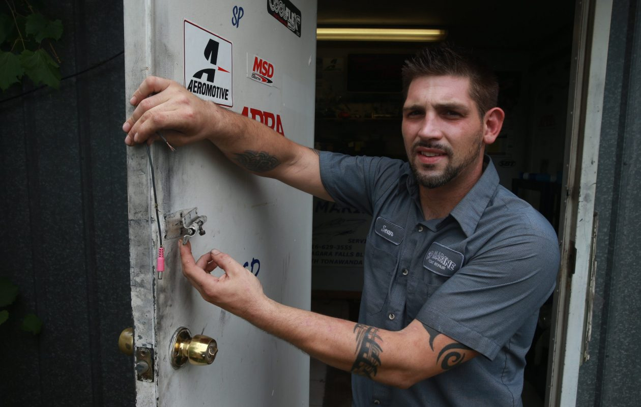 Sean Polley, owner/master mechanic at SP Marine in Tonawanda, shows a broken deadbolt and wires from a security video camera that were damaged on Monday, July 11, 2016. (John Hickey/Buffalo News)