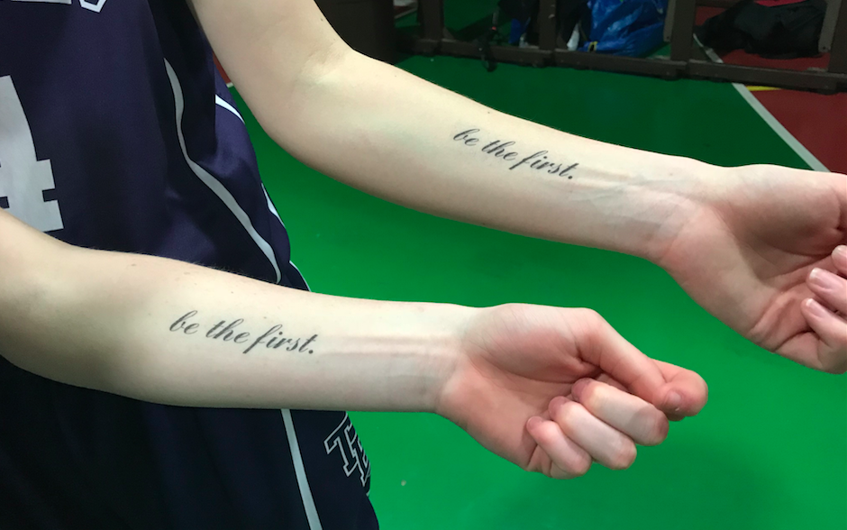 Danielle, foreground, and Allyson Haskell show off their team's temporary 'be the first.' tattoos.