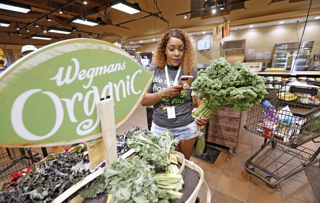 Instacart shopper Brianna Johnson of Buffalo shops a customer's order at the Wegman's location on Alberta Drive in Amherst when the program rolled out in August. Shopper pay has been cut by more than half since then.  (Robert Kirkham/News file photo)