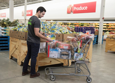 An Instacart employee selects fresh produce at BJ's Wholesale Club in Waltham, Mass. on March 13, 2018 for same-day delivery to BJ's members as part of the companies' expanded partnership. (Christine Hochkeppel/PRNewsfoto)