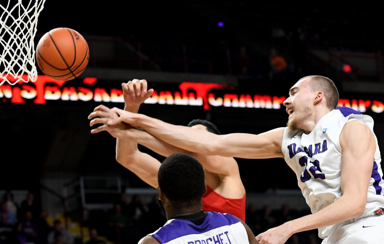 Dominic Robb, right, and Marvin Prochet, center, block an attempt by Tyler Nelson of Fairfield University during MAAC  basketball quarterfinals. (Albany Times Union)