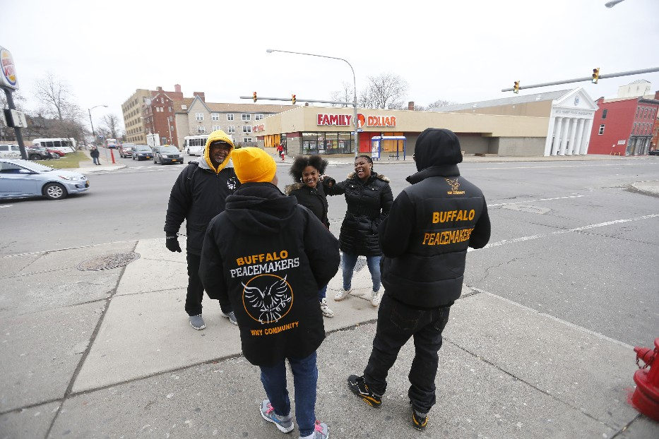 Buffalo Peacemakers Claude Lidge, left, Ella Martin, second left, and James Carraway, right, talk with students Tyiona Pettigrew, left, and Davida Simmons after school on the corner of Main and Utica streets. (Mark Mulville/Buffalo News)