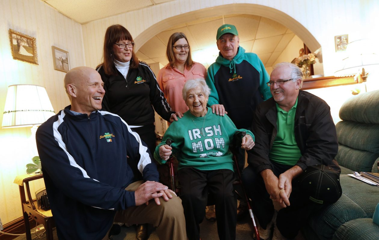 Longtime organizers of the Shamrock Run in the Old First Ward gather in the living room of Doris Bouquard (center), who once opened her doors to runners as part of registration. From left, in front, Mike Malaney, Doris and Bill Conway. Back from left, Donna Carroll, Maryann Schuta and Earl Wells. (Robert Kirkham/Buffalo News)