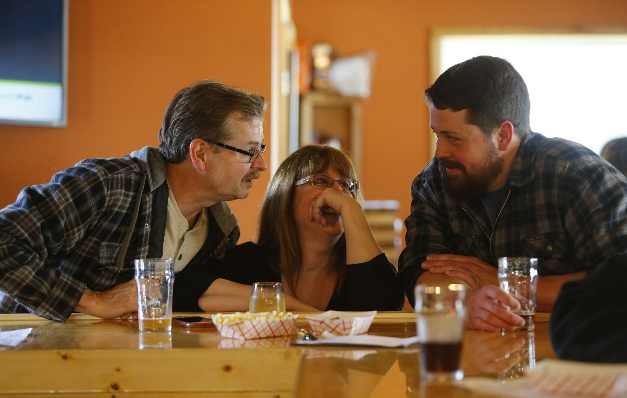 Scott Brownlie, left, Karen Brownlie, center, and Mike Van Lew, right, share a conversation and a pint at the Windy Brew in Strykersville. (Mark Mulville/Buffalo News)