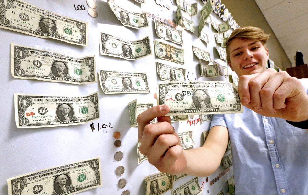 Accidental hero Dylan Belscher shows the found dollar bill that started an unlikely campaign in an English class at John F. Kennedy High School, in Cheektowaga. (Robert Kirkham/Buffalo News)
