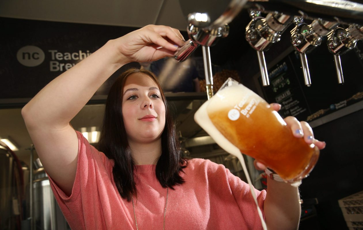 Niagara College Teaching Brewery in Niagara-on-the-Lake, Ont., is among more than 30 breweries in Western New York and Southern Ontario that have collaborated on craft beers.  Karen Belfry, above, pours one of the house brands in the teaching brewery's tasting room. (Sharon Cantillon/News file photo)