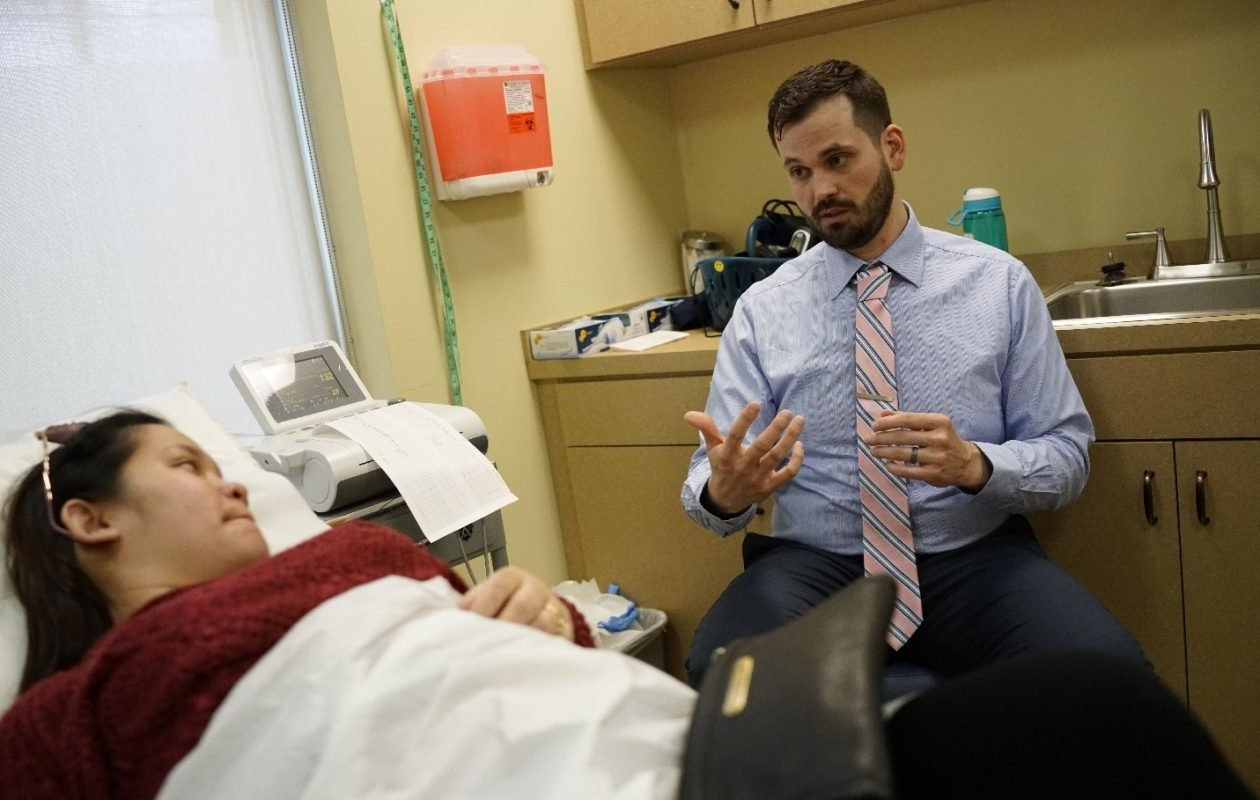 Dr. Ethan Gable, the new chief medical officer at Jericho Road Community Health Center, talks with pregnant patient Scarllette Cooper about what to expect in the coming weeks. (Derek Gee/Buffalo News)