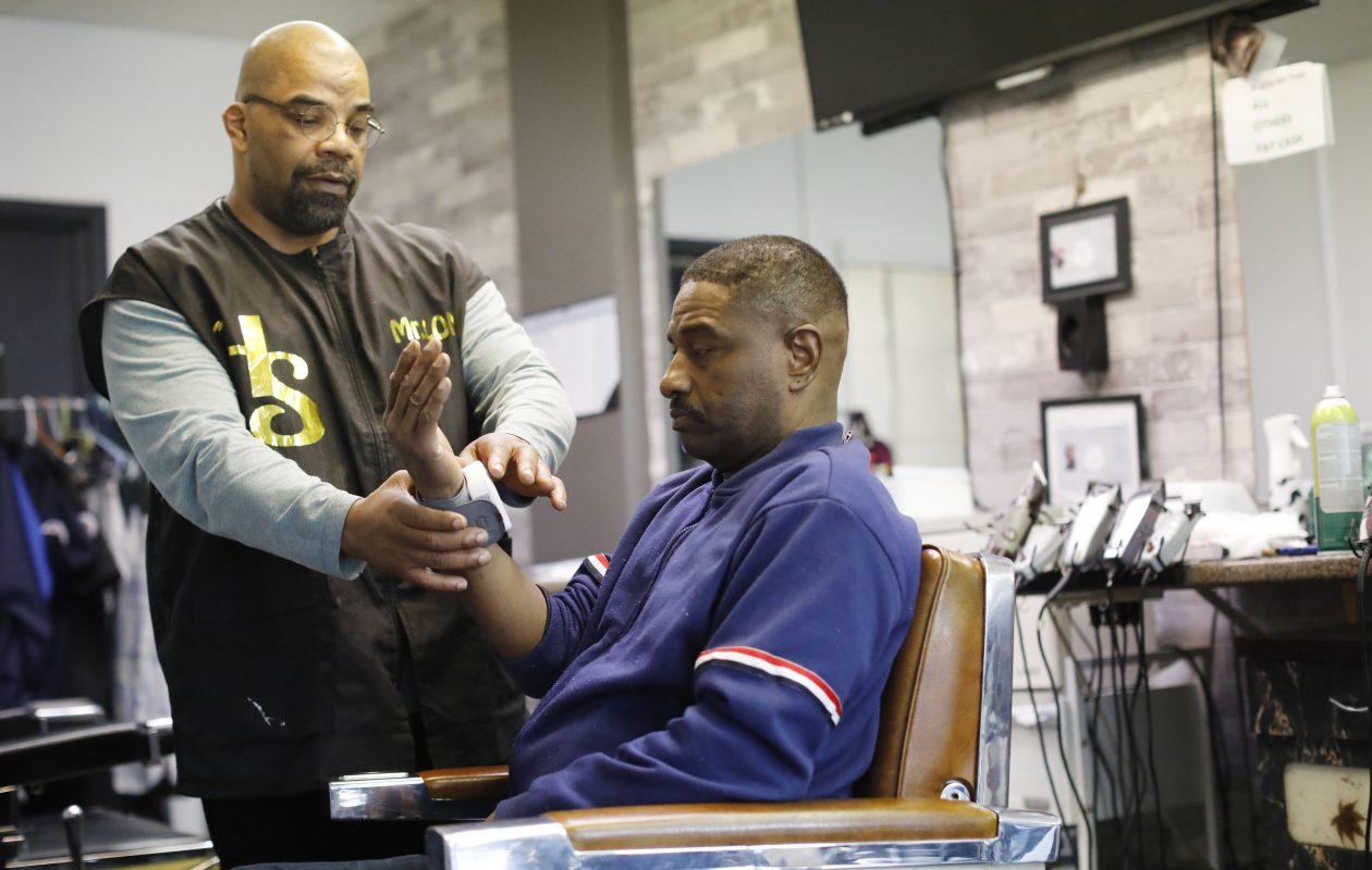 Master Barber Lonnie Green puts a blood pressure cuff on customer Michael Clark as he sits for a haircut at HeavenSent Community Barbershop as part of a new outreach effort to bring blood pressure monitoring and heart health awareness into barbershops and hair salon. (Derek Gee/Buffalo News)