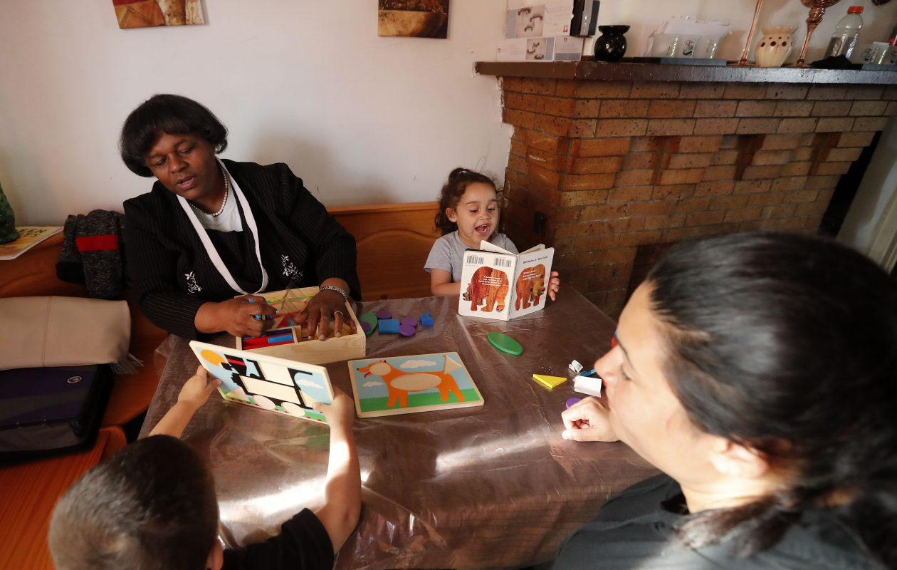 Vanessa Birmingham works with children Yamilette Santiago, right, her brother Jomar Perez, bottom left, and their mother Yesenia Santiago in the Parent-Child Home Program. (Mark Mulville/Buffalo News)