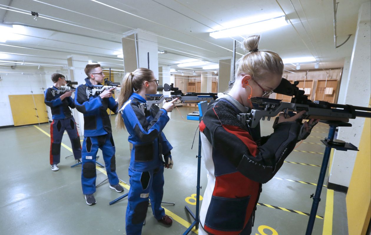 Members of the Kenmore combined air rifle team – from right, Bailey Begovich, Holly Kaiser, Chris Donn and Austin Orlowski – take aim during a practice session at Kenmore East High School. A bill in the state Assembly would ban schools from having such teams. (Robert Kirkham/Buffalo News)