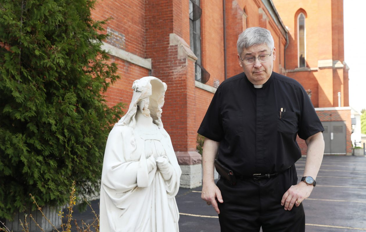 The Rev. Mike Burzynski with the statue of Mary after it was vandalized at St. John Kanty Church. (John Hickey/Buffalo News)